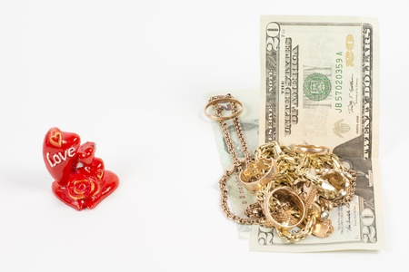 Conceptual image of a collection of gold jewellery, a red rose love ornament and money photo