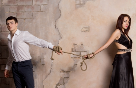 Conceptual shot of man and woman pulling a rope photo
