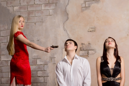 Beautiful blonde woman in a red dress threatening two young hostages who are kneeling in front of her with a handgun photo