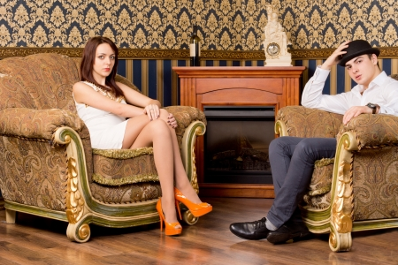 Stylish young couple having drinks seated in two ornate vintage armchairs in a luxury living room photo
