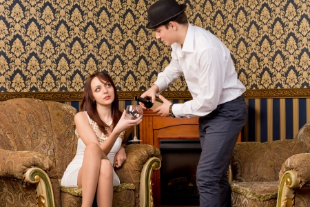 Fashionable young man pouring his girlfriend some wine as she sits in a vintage armchair in an ornate living room photo