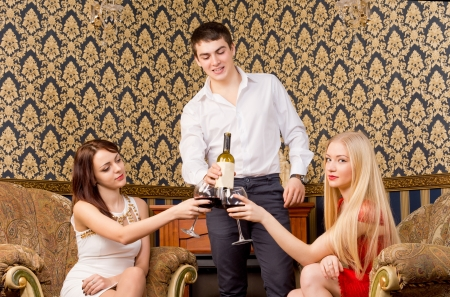 Handsome young man serving wine to two glamorous young ladies seated together in vintage armchairs photo