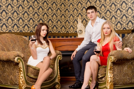 Three stylish fashionable young friends seated in elegant surroundings enjoying a night out together photo