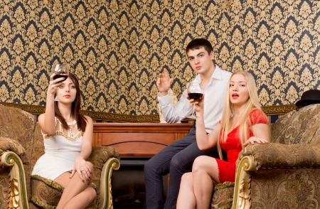 Three happy stylish young friends raising their glases and toasting with wine in elegant surroundings photo