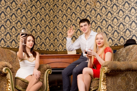 Three smiling elegant young friends sitting in vintage armchairs celebrating raising their glasses to the camera in a toast photo