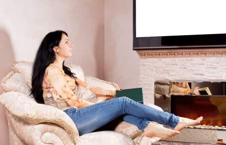 Attractive young woman relaxing in a comfortable upholstered armchair daydreaming in front of the fire photo