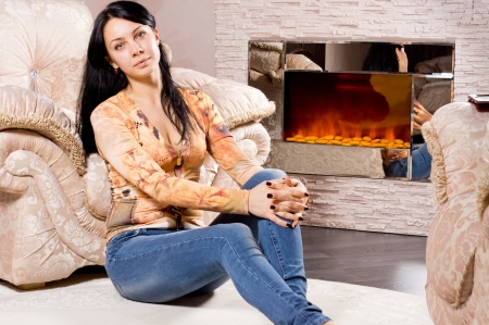 woodburner: Attractive young woman in jeans relaxing in front of a warm fire sitting on the floor leaning against an upholstered armchair looking at the camera