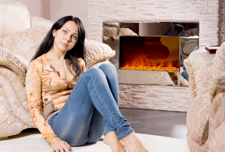 woodburner: Serious attractive woman relaxing at home sitting on the floor in front of a warm winter fire resting her back against a comfortable armchair Stock Photo