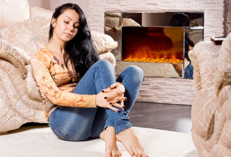woodburner: Casual woman relaxing in the warmth of a fire sitting cross legged on the floor enjoying the peace and tranquillity