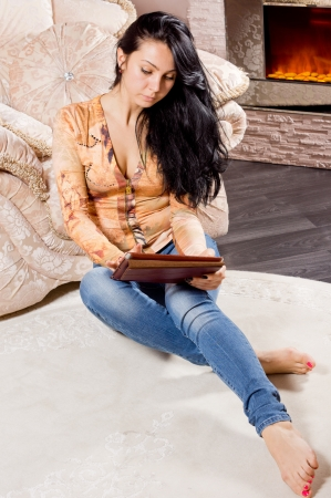 woodburner: Smart casual young woman with long brunette hair relaxing sitting on the floor in front of a warm fire working on a tablet Stock Photo