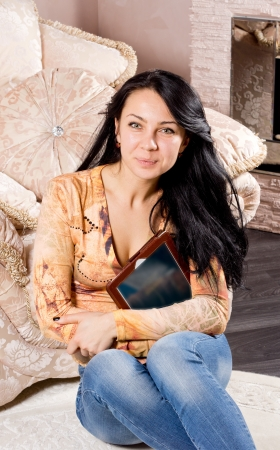 woodburner: Smiling casual woman in jeans relaxing on a carpet with her back against an upholstered armchair looking at the camera with a tablet clutched to her chest