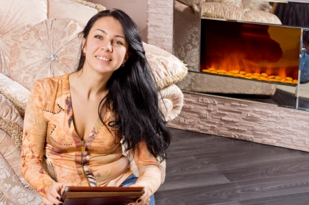 woodburner: Smiling beautiful young woman sitting on the floor relaxing in front of a warm winter fire