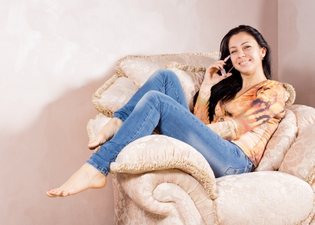 Happy smiling young woman chatting on a mobile phone while relaxing in a big comfortable upholstered armchair photo