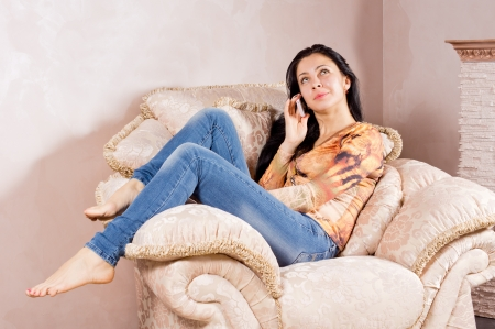 Beautiful casual barefoot young woman listening to a conversation on her mobile phone while relaxing in a comfortable cream armchair photo