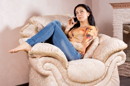 Casual young woman relaxing with her bare feet dangling over the arm of a large upholstered armchair chatting on a mobile photo