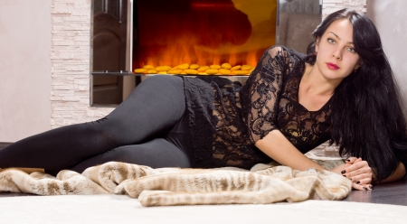 woodburner: Glamorous young woman in a lacy black top and slacks lying on a fur coat in front of a fire resting on her elbow looking at the camera Stock Photo