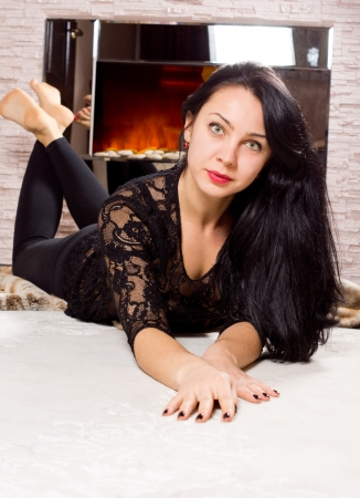 woodburner: Sexy beautiful woman in a lacy black top with long brunette hair lying facing the camera on a light coloured carpet in front of a blazing fire