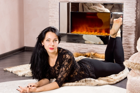 woodburner: Beautiful sexy barefoot woman lying on a carpet in front of a blazing fire wearing a lacy black top looking at the camera Stock Photo