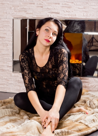 woodburner: Beautiful young woman in a stylish black outfit sitting in front of a fire on a fur coat on the floor Stock Photo