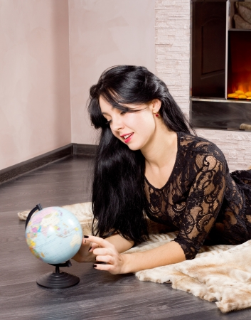 woodburner: Beautiful woman lying on the floor in front of a fire playing with a globe with a sweet smile on her face as she recalls memories of her summer vacation