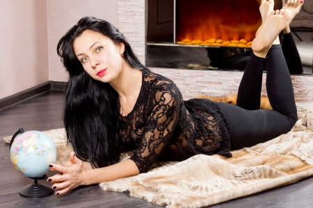 woodburner: Attractive barefoot young woman lying in front of the fire with a globe in front of her dreaming of her summer vacation and travels