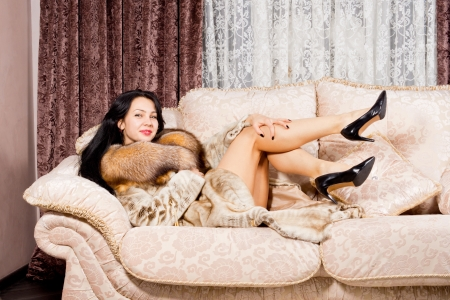 Sexy woman in fur coat and high heels reclining on a couch with her legs in the air smiling at the camera photo