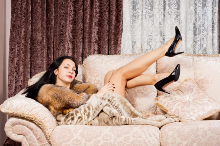 Sexy beautiful woman lying on a cream sofa in a fur coat kicking her long bare legs in the air while looking at the camera photo