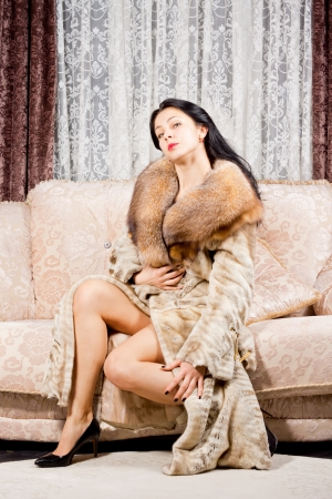 Glamorous sophisticated young woman in a fur coat sitting on a sofa in her living room with a backdrop of lace curtains looking at the camera photo