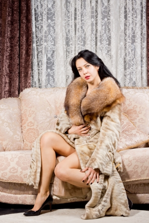 Glamorous beautiful woman sitting looking at the camera while posing on a couch in bare legs and a fur coat photo