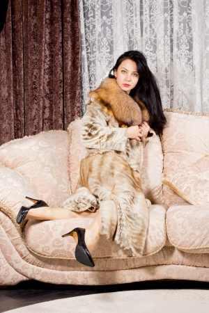 Elegant wealthy woman with long brunette hair sitting comfortably on an upholstered sofa clutching her luxurious fur coat around her photo