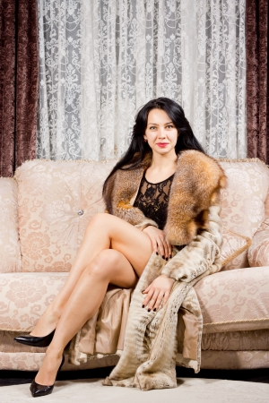 legs crossed: Glamorous smiling sophisticated woman posing on a sofa with her long bare legs crossed in an elegant luxurious fur coat in a stylish living room