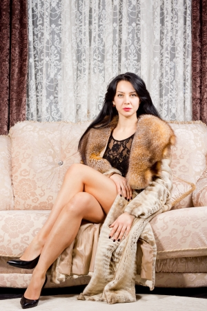 Glamorous young woman with her sexy long bare legs crossed in front of her posing sitting in a fur coat on a sofa in an elegant living room photo