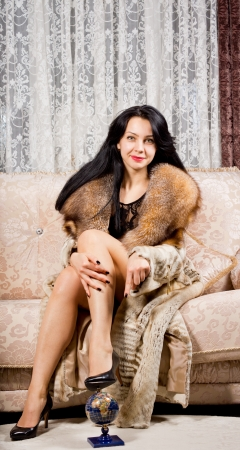 Beautiful smiling elegant woman posing on a cream sofa in a stylish living room in a luxurious fur coat photo