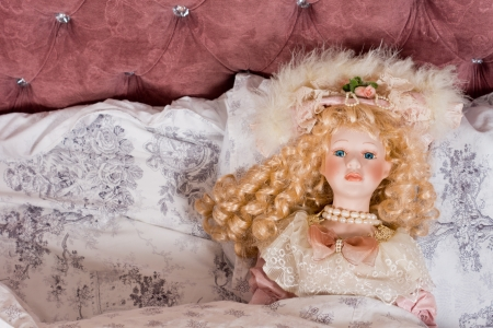 ringlets: Face of a beautiful vintage doll with her long blonde hair in ringlets and wearing pearls and a fancy hat lying on a bed under the bedclothes