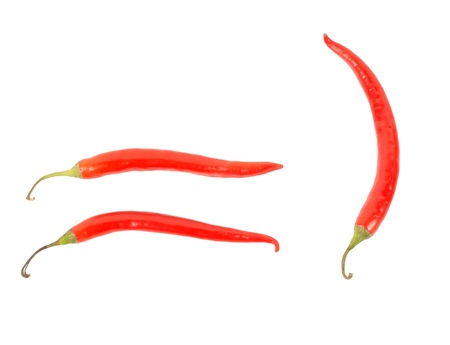 flavouring: Three red hot chilli, or chili, peppers isolated on a white background used in cooking as a pungent seasoning and flavouring and as a dried spice
