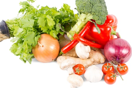 Pile of assorted farm fresh vegetables, spices and herbs with onions, broccoli, tomatoes, bell pepper, mushrooms, chilli pepper, ginger and flat leaf parsley on a white background with copyspace Stock Photo - 18523753