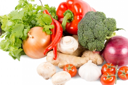 Assorted fresh organic vegetables, spices and herbs with garlic, onions, broccoli, tomatoes, bell pepper, mushrooms, chilli pepper, ginger and flat leaf parsley on a white background Stock Photo - 18523757