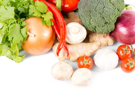 Farm fresh organic vegetables with an assortment of broccoli, mushrooms, chilli peppers, onions, parsley, ginger and tomatos on a white background Stock Photo - 18523759