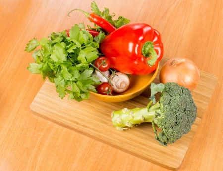 High angle view of a bowl of farm fresh vegetable ingredients ready for cooking on a wooden chopping board including broccoli, bell pepper, parsley, mushrooms, onions, chilli pepper and tomato Stock Photo - 18523784