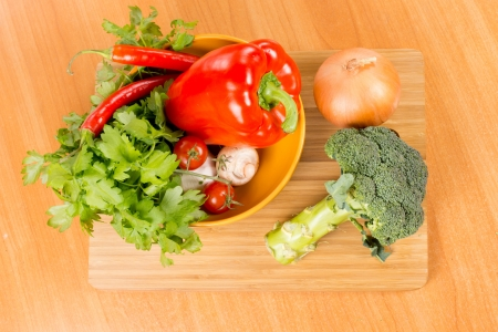 Fresh vegetables on a chopping board with broccoli and an onion and a bowl containing bell pepper, parsley, tomato, chilli pepper and mushrooms on a wooden kitchen table Stock Photo - 18523785