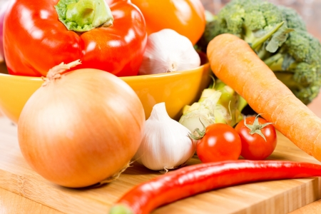 Colourful farm fresh vegetables on a wooden kitchen countertop including garlic, broccoli, bell pepper, mushrooms, onions, chilli pepper and tomato Stock Photo - 18523746