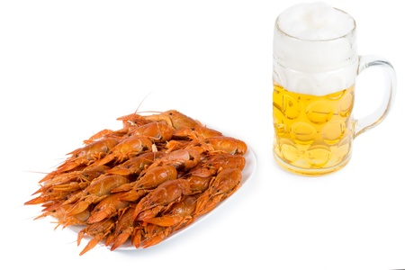 Plate of delicious cooked whole unshelled cooked prawns and a frothy pint of beer in a glass tankard isolated on white photo