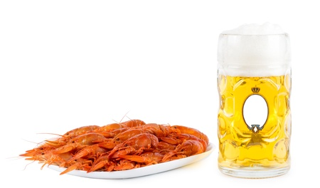 Seafood platter of cooked whole prawns with a glass of frothy golden ale or beer in a glass tankard with a blank badge on the exterior photo