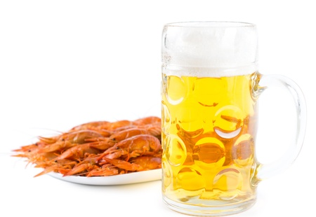 Glass of golden frothy beer served with a seafood platter of delicious cooked whole unshelled prawns on a white background photo