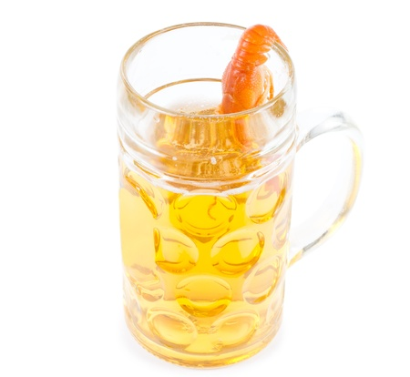 Fun image of a thirsty prawn with a taste for beer with its tail hooked on the rim of the glass tankard and the body inside as it reaches down towards the surface of the drink photo