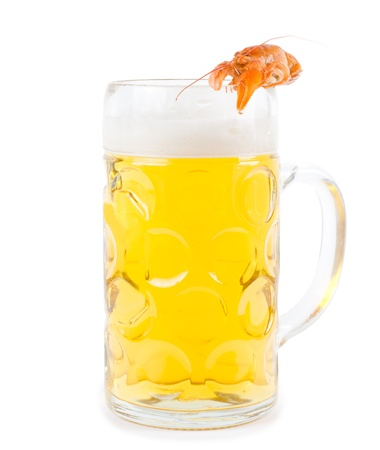 Frothy glass of light golden beer with a single cooked pink prawn balanced carefully on the rim isolated on white photo