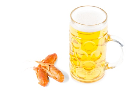 Glass of frothy light golden ale or beer together with three delicious cooked whole prawns isolated on white photo