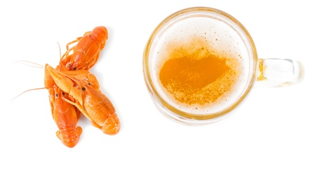 Overhead view of three tasty whole cooked prawns served together with a glass tankard of golden ale or beer on a white background photo