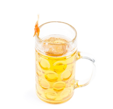 Cooked unpeeled prawn balanced on the rim of a glass beer mug full of light golden ale or of beer on a white background photo