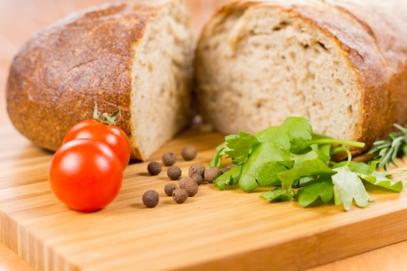 Wheat bread with herbs and tomatoes on a wooden board Stock Photo - 18572650